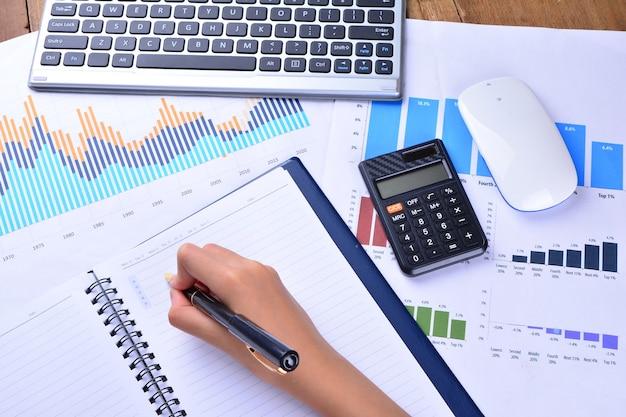 Ręczne pisanie na pustym notatniku z wykresem, wykresem, klawiaturą, myszą i kalkulatorem na drewnianym stole