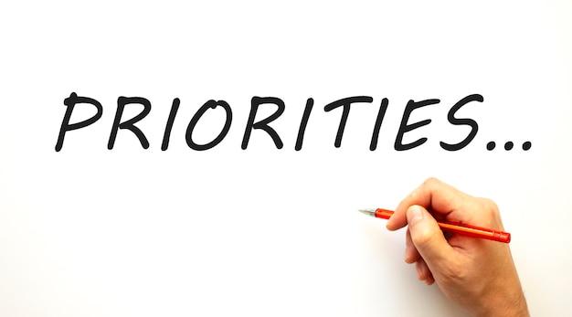 Ręczne pisanie priorytetów za pomocą pióra. na białym tle pomysł na biznes.