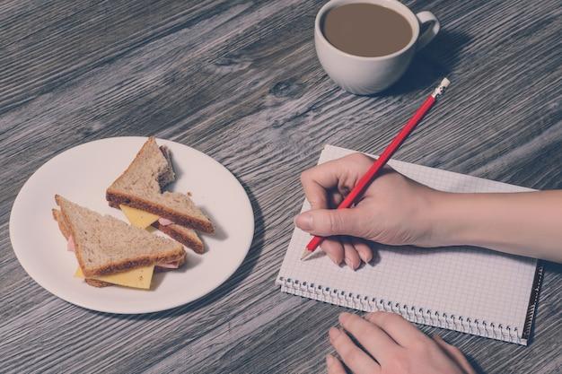 Ręczne pisanie w zeszycie. przerwa w pracy. tło kanapka z serem na talerzu i filiżankę kawy. widok z góry, styl vintage