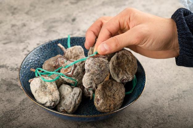 Ręczne pobieranie suszonych owoców persymony na kamiennej powierzchni