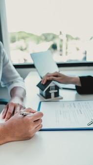 Ręczne podpisanie umowy po tym, jak agent nieruchomości wyjaśni kupującemu umowę biznesową