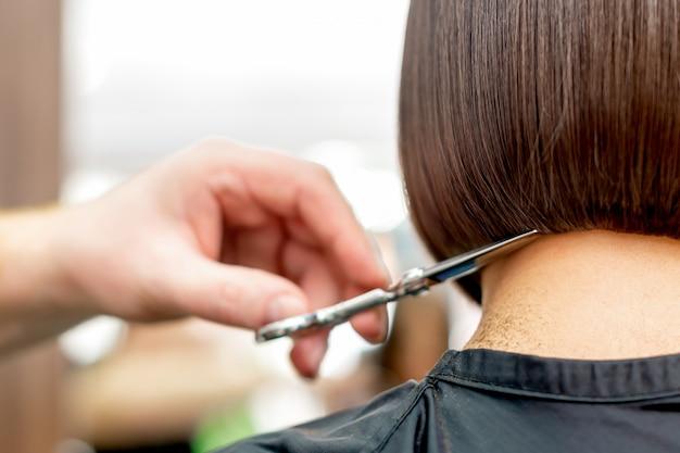 Ręczne strzyżenie końcówek włosów przez fryzjera.