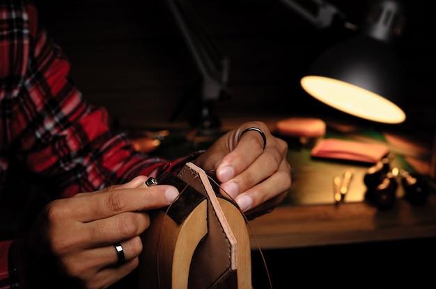 Ręczne szycie skóry garbowanej roślinnie. skóra i narzędzia rzemieślnicze.
