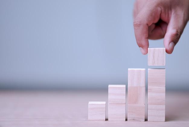 Ręczne trzymanie i układanie drewnianych bloków jako krok z miejscem na zawartość w drewnianym bloku