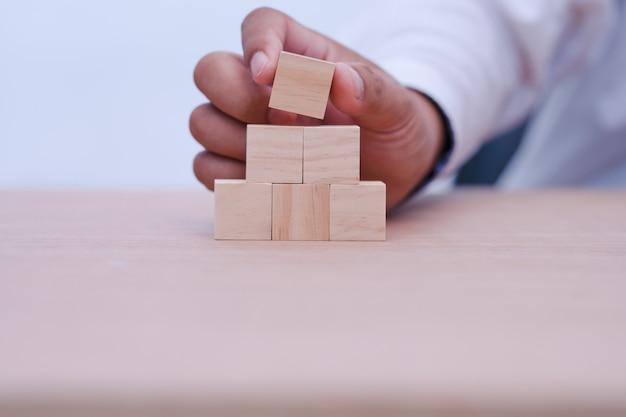 Ręczne trzymanie i układanie drewnianych bloków jako schodów z miejscem na zawartość w drewnianym bloku