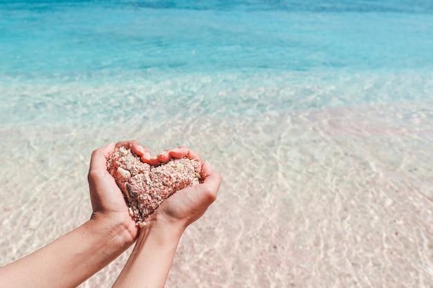 Ręczne tworzenie kształtu serca z różowego piasku z przezroczystą wodą na plaży