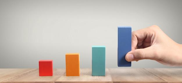 Ręczne układanie bloku drewna w formie wykresu. proces wzrostu koncepcji biznesowej