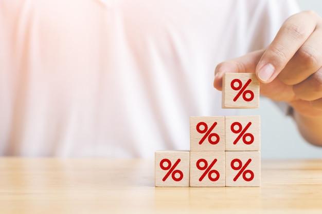 Ręczne umieszczanie drewnianego bloku kostki rosnącej na górze z symbolem procentu ikony