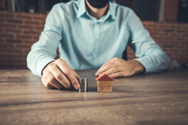 Ręczne umieszczanie monet na stosie z modelem domu. oszczędność pieniędzy na zakup domu