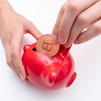 Ręczne wkładanie monety bitcoin do czerwonej skarbonki, zbliżenie. koncepcja oszczędzania pieniędzy elektronicznych bitcoin. koncepcja kryptowaluty bitcoin. koncepcja wirtualnej waluty
