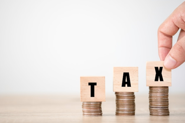 Ręczne wprowadzanie sformułowania podatkowego, które są drukowane na drewnianych kostkach na stosach monet. koncepcja zwiększenia podatków i kadzi.