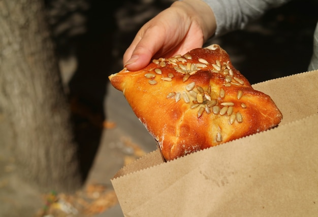 Ręczne wybieranie ciasta francuskiego z papierowej torby, koncepcja ratowania ziemi za pomocą nieplastikowych torebek