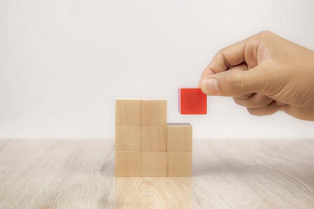 Ręczne wybieranie zabawki z drewnianymi klockami z czerwonej kostki ułożonej bez grafiki.
