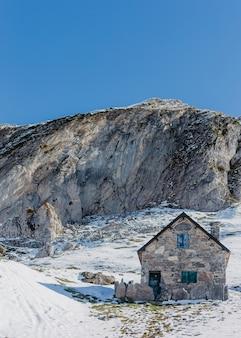 Ręcznie budowany szary kamienny dom z wysokimi skałami i pięknym jasnym niebieskim niebem w tle