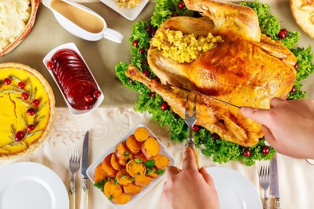 Ręcznie krojony pieczony cały indyk na obiad z okazji święta dziękczynienia.