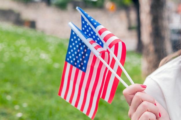 Ręcznie macha flagą amerykańską.