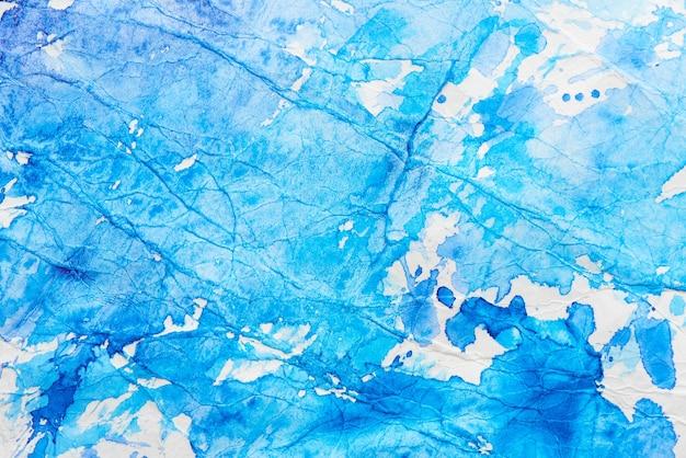 Ręcznie malowane niebieskie abstrakcyjne plamy akwarela na białym papierze. tło powitalny farby