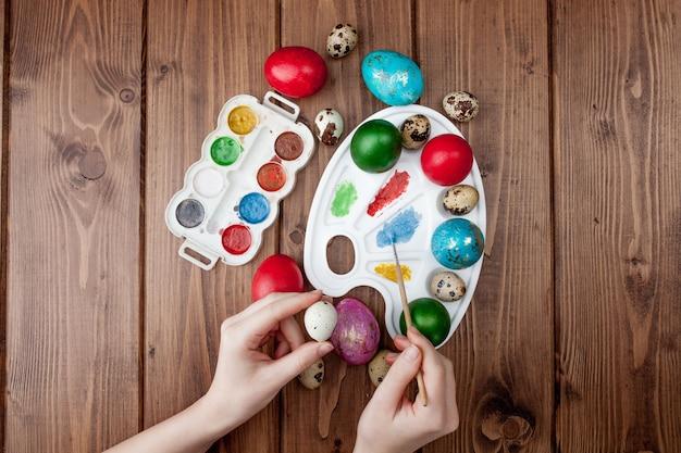Ręcznie malowane pisanki, farby i pędzle na drewniane tła. przygotowanie do wakacji. ręce dziewcząt narysuj wzór