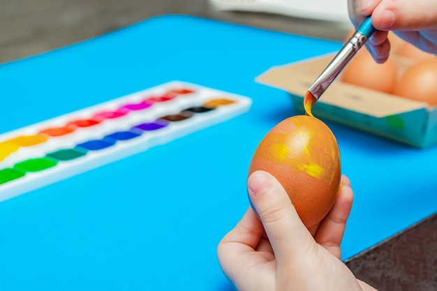 Ręcznie malowane pisanki przed wielkanocą. przygotowanie do wielkanocy, na niebieskim tle. wielobarwna farba, kopia przestrzeń.