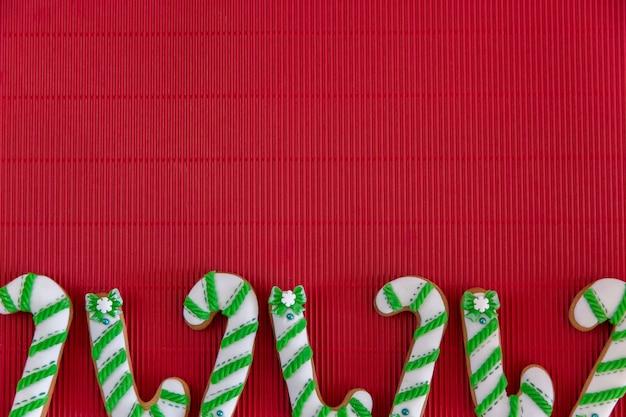 Ręcznie malowany świąteczny piernikowy zielony i biały cukierek trzcina cukrowa i płatki śniegu na pięknym czerwonym tle. koncepcja karty. widok z góry. leżał płasko.