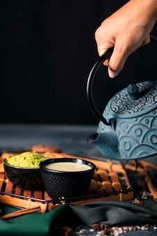 Ręcznie nalewając herbatę matcha na filiżanki