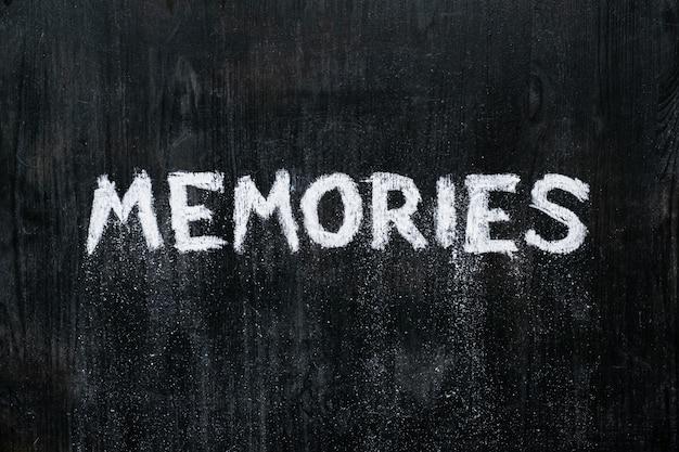 """Ręcznie napisane słowo """"wspomnienia"""" rozpadające się na tablicy"""