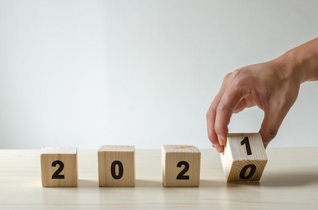 Ręcznie odwróć drewniany klocek z rokiem 2020 i 2021. szczęśliwego nowego roku 2021