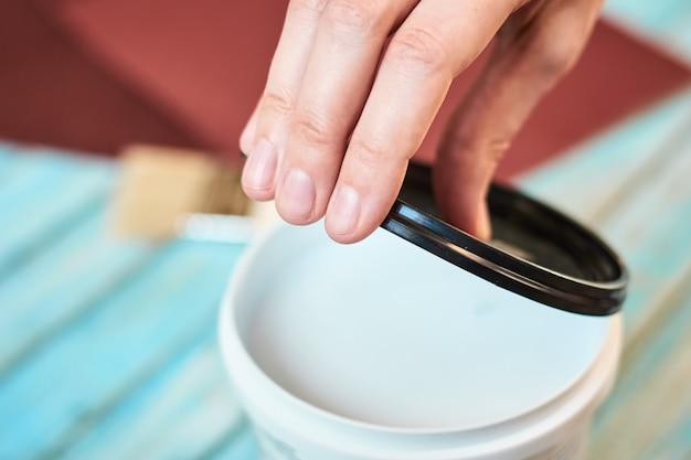 Ręcznie otwórz puszkę białej farby i drewniane deski przygotowujące się do malowania
