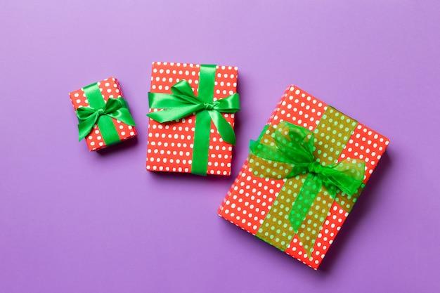 Ręcznie owinięty świąteczny lub inny świąteczny prezent w papierowej zielonej wstążce na fioletowo. pudełko, prezent na kolorowym stole, widok z góry