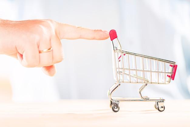 Ręcznie pchający czerwony wózek na zakupy z palcem. koncepcja zakupów.