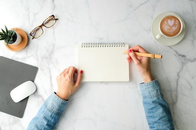 Ręcznie pisać na notatniku do terminarza ręka z filiżanką kawy i stacjonarna z miejsca na kopię widok z góry. nowoczesny styl. widok z góry.