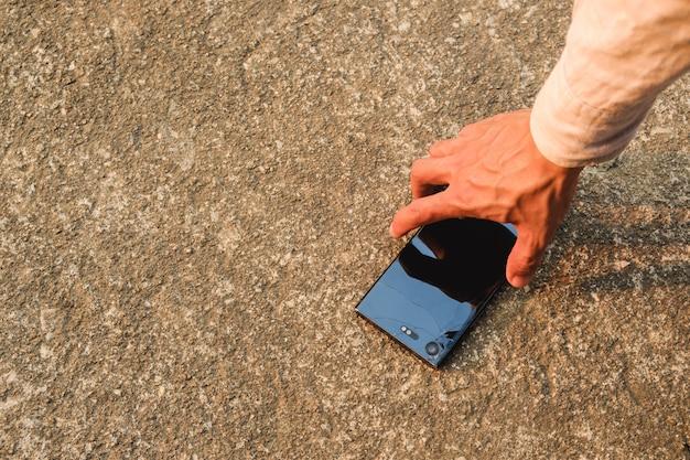 Ręcznie podnieś telefon upuszczony na ziemię, co spowoduje jego uszkodzenie.