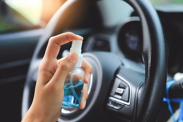 Ręcznie pompowany żel alkoholowy do czyszczenia kierownicy przed użyciem samochodu w ciągu dnia od ucieczki vocid lub wirusa corona. ludzie dbają o życie dzięki wirusowi corona.