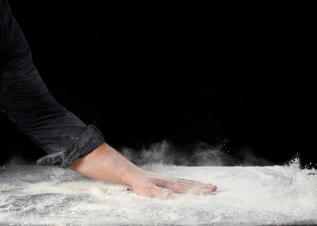 Ręcznie posypuje mąkę pszenną białą w różnych kierunkach