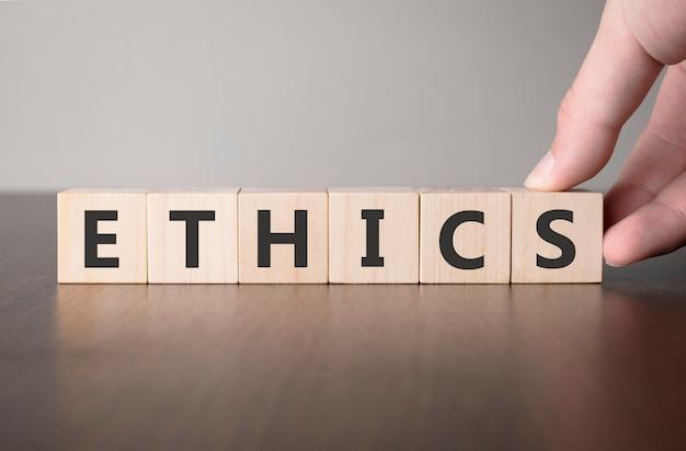 Ręcznie przerzuć drewnianą kostkę ze słowem etyka. inwestycja w koncepcję ubezpieczeń na życie i opieki zdrowotnej