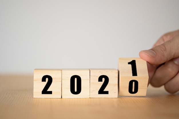 Ręcznie przerzucaj drewniane klocki na rok zmiany 2020 do 2021. koncepcja nowego roku i wakacji.