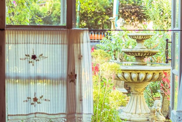 Ręcznie robiona biała zasłona z widokiem z okna na fontannę i zieleń z tła ogrodu drzewnego