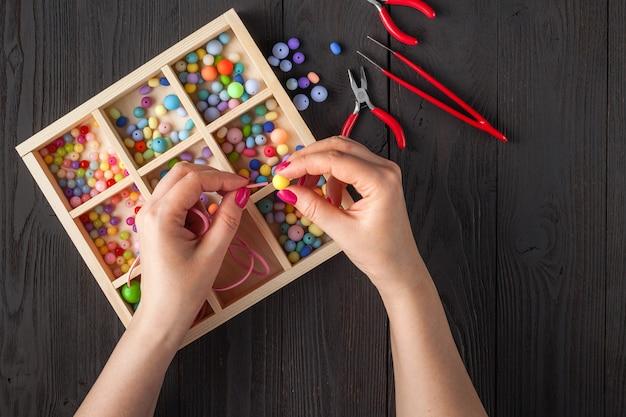 Ręcznie robiona bransoletka z guzikami. zestaw jasnych kolorowych przycisków, szczypce. pomysł na biżuterię diy. łatwe tworzenie kreatywnych rzemiosł