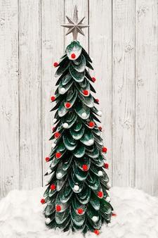 Ręcznie robiona choinka z plastikowych łyżek ozdobiona wielokolorowymi miękkimi zabawkami świątecznymi i mieni się na jasnej drewnianej ścianie. drzewo noworoczne.
