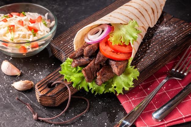 Ręcznie robiona chusta shawarma leży na drewnianej desce do krojenia