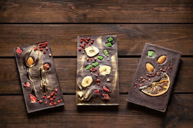 Ręcznie robiona ciemna czekolada z migdałami, pomarańczą, orzechami laskowymi, bananem i suszonymi owocami na drewnianej powierzchni