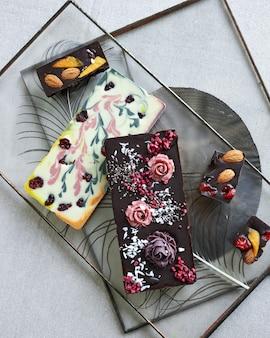 Ręcznie robiona czekolada widok z góry na różne słodycze, składniki do gotowania i narzędzia rzemieślnicze na czarnym stole. mała firma, koncepcja ręcznie robionych cukierków