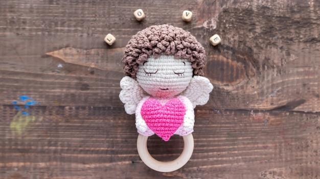 Ręcznie robiona dzianinowa zabawka dla dzieci z drewnianymi literami tworzącymi słowo miłość. widok z góry