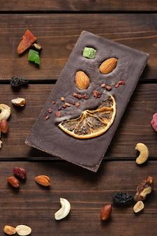 Ręcznie robiona gorzka czekolada z migdałami, pomarańczą i suszonymi owocami na drewnianym tle