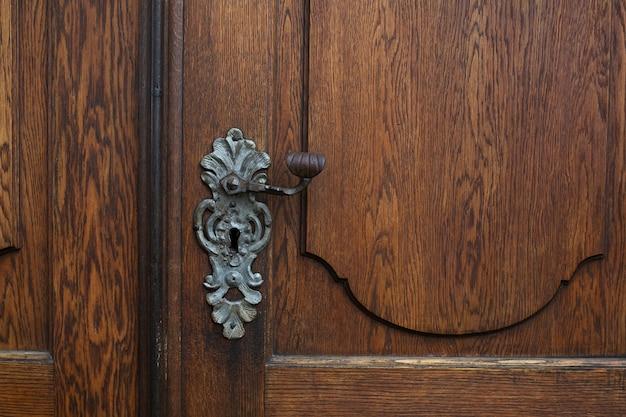 Ręcznie robiona klamka na brązowe drewniane drzwi. strzał zbliżeniowy