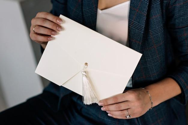 Ręcznie robiona koperta prezentowa w rękach kobiet. opakowanie wakacyjne zaproszenia ślubne.