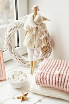 Ręcznie robiona lalka i pianki w pobliżu okna. przytulny zimowy poranek. świąteczny koncept i nastrój.