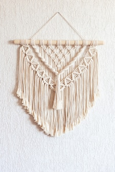 Ręcznie robiona makrama. dekoracja ścienna ze 100% bawełny z drewnianym patyczkiem zawieszonym na białej ścianie.