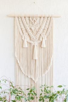 Ręcznie robiona makrama. dekoracja ścienna ze 100% bawełny z drewnianym zawieszeniem na białej ścianie.