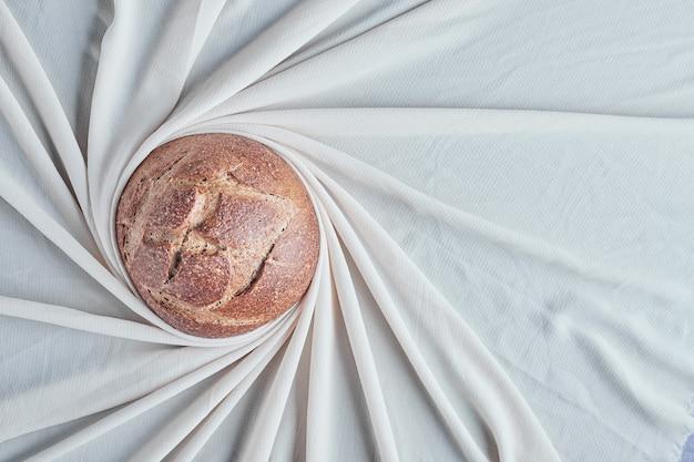 Ręcznie robiona okrągła bułka na szarym obrusie.